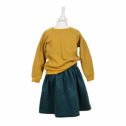 Bio Sweater für Kinder senfgelb kombiniert mit einem Cordrock in petrol